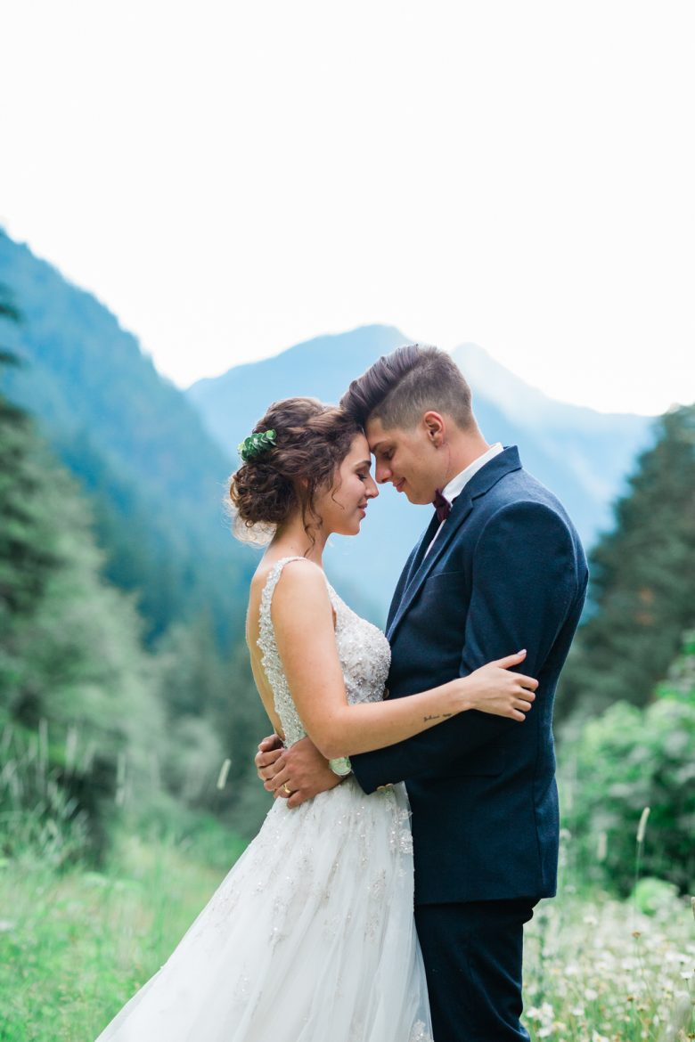 bride & groom in front of a backdrop of mountains and trees