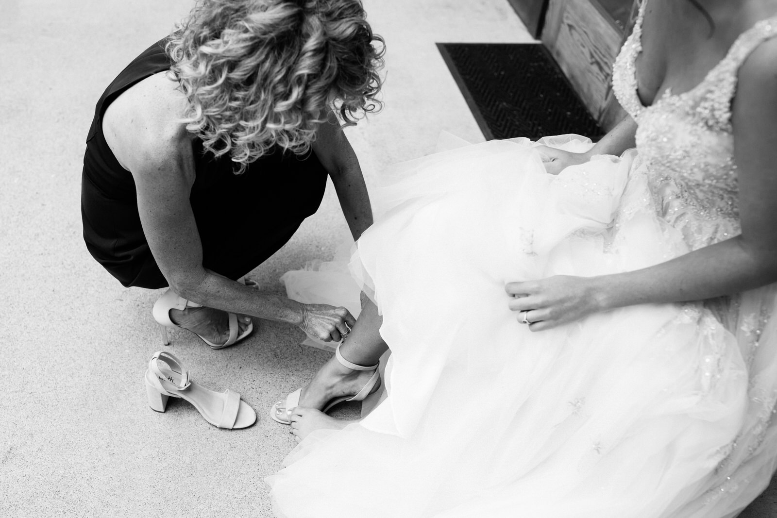Mother putting on her daughters bridal shoes