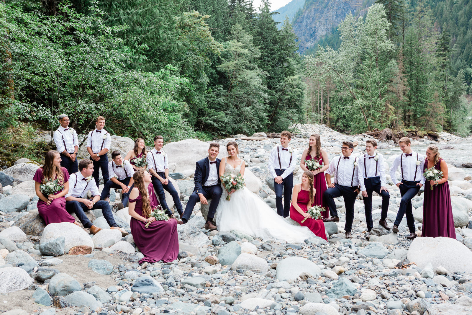 large bridal party poses on rocks by the river