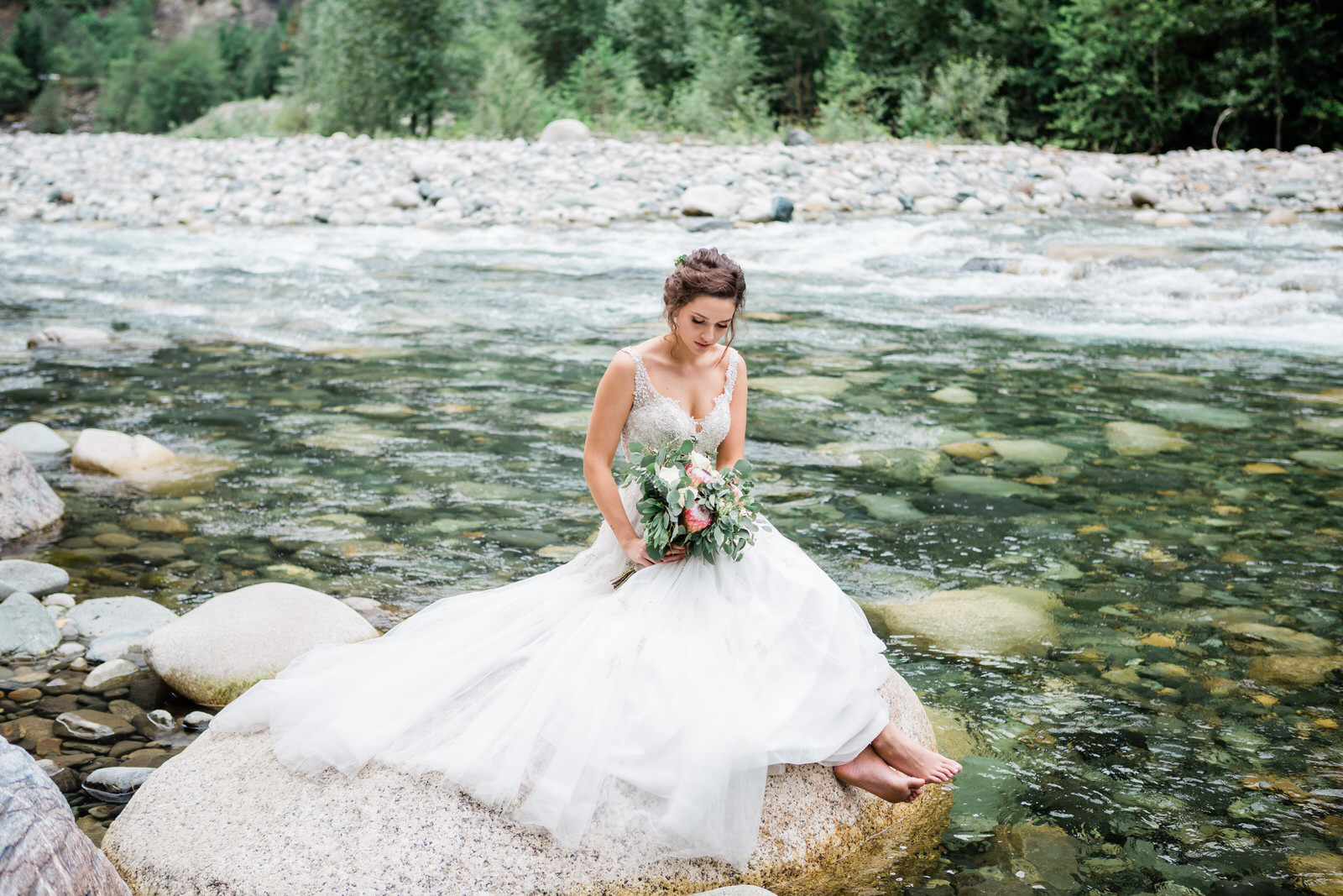 bridal portrait sitting on a rock by the river