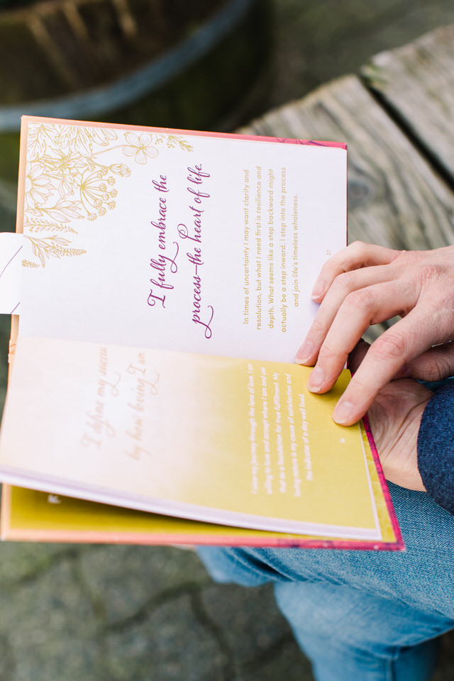 hands holding a book open to a page about embracing the process of life
