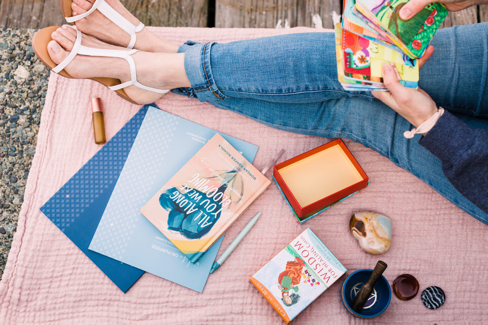 Woman sitting on a blanket holding daily affirmation cards and beside other Morning Routine Items like a journal
