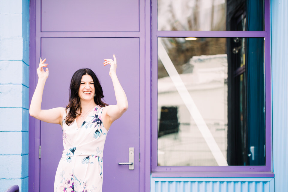 Woman wearing floral jumpsuit dancing in front of a purple door and blue building
