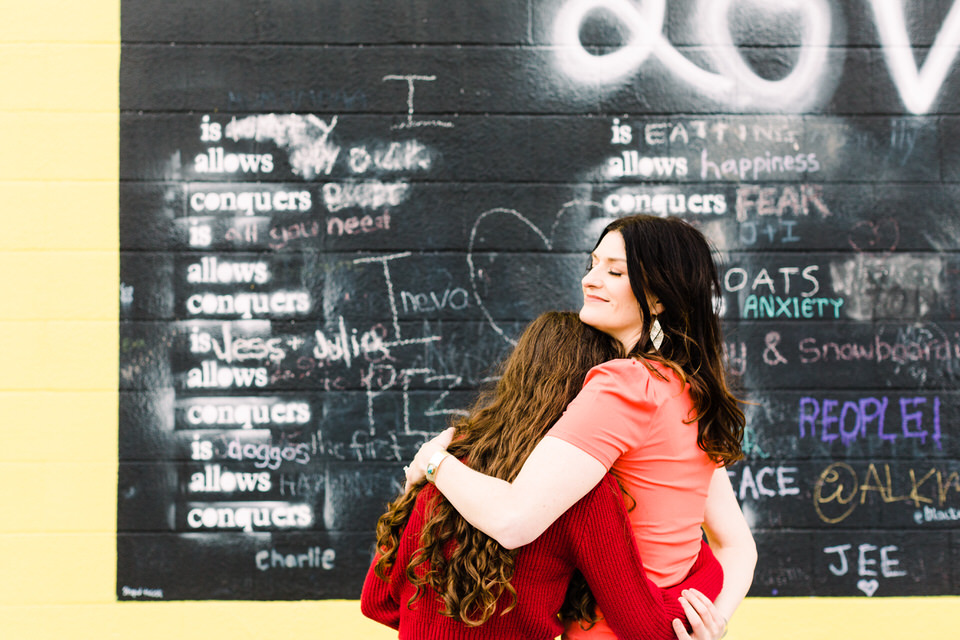 Mother and Daughter embracing in front of a Love Conquers sign
