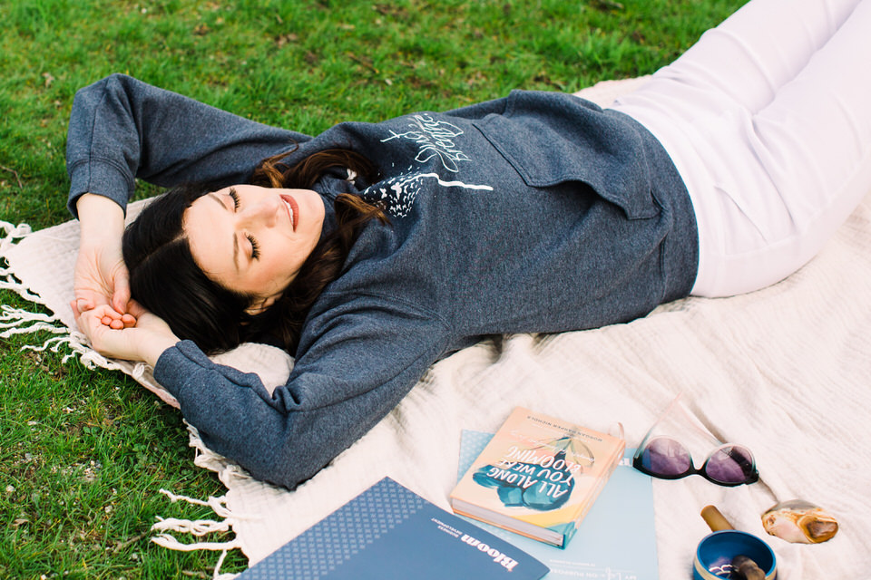 Woman laying on blanket on the grass with her journal and sunglasses beside her
