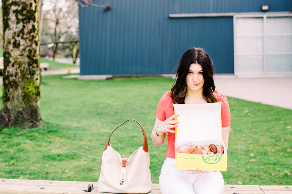 Woman sitting on bench with purse beside her and she's holding a box of donuts contemplating eating them