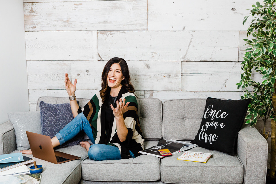 Woman sitting on couch beside laptop tossing her hands in the air