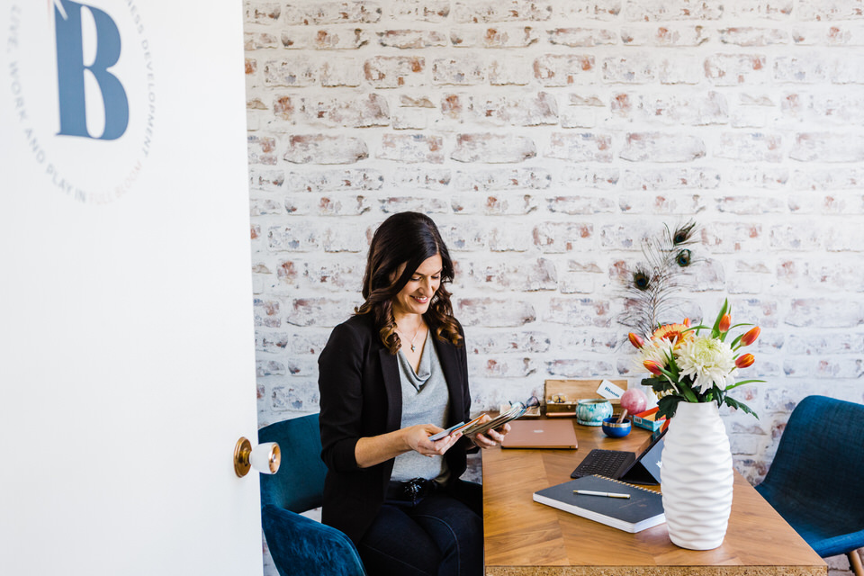 Woman sitting at desk reading and enjoying her time
