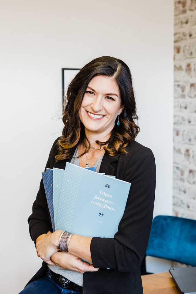 Woman holding booklets smiling