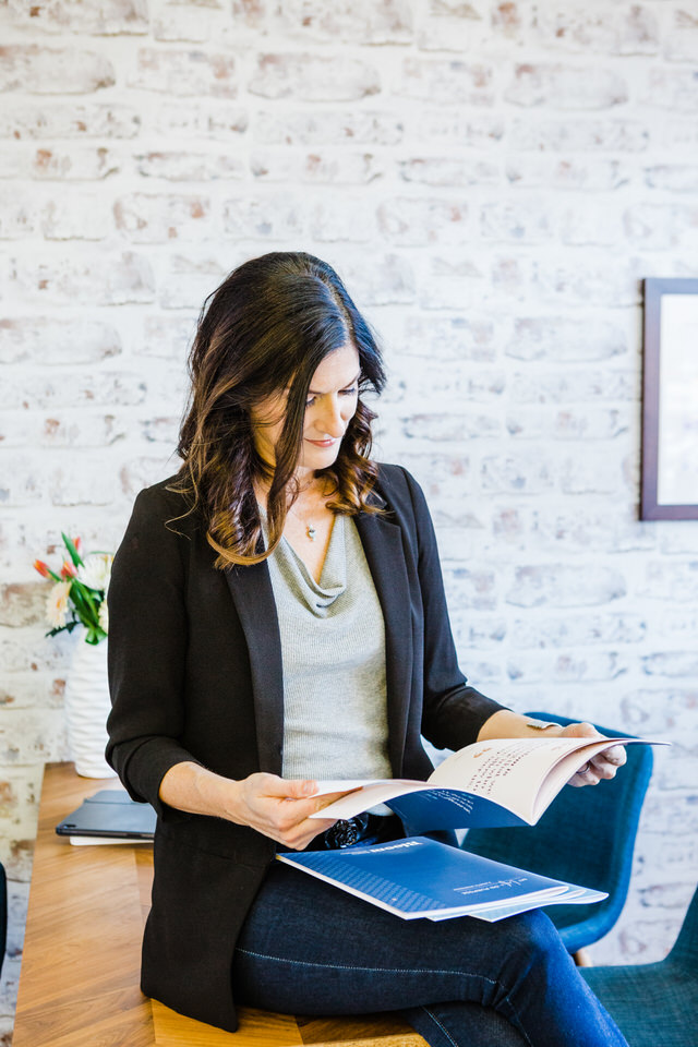 Woman sitting on her desk reading a booklet