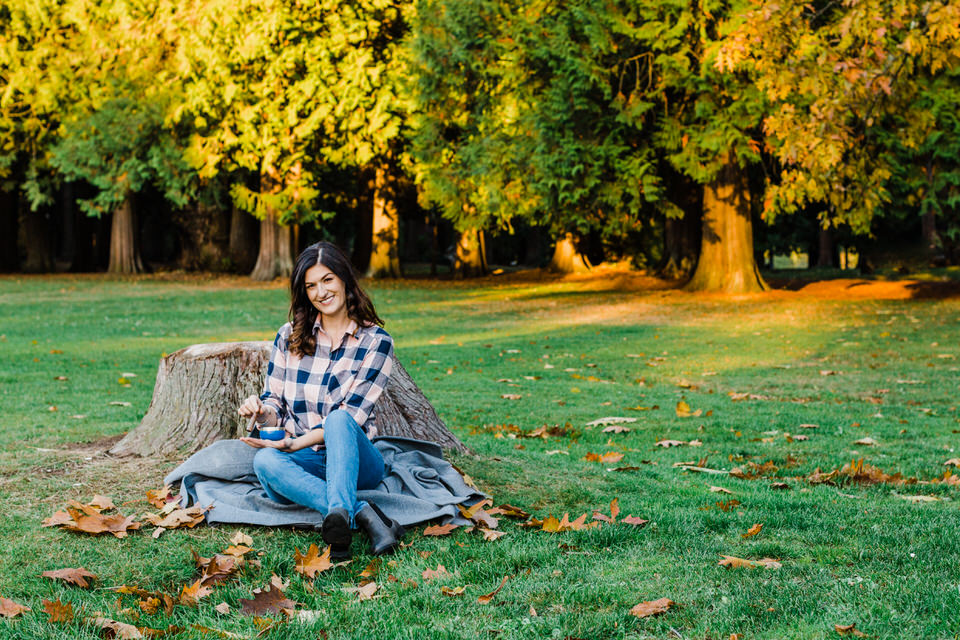 Woman sitting on blanket, leaning on stump in a park