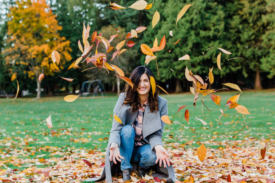 Woman kneeling in pile of leaves and tossing in the air