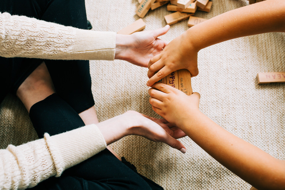 Therapist sitting on floor holding out hands to a child holding some therapy blocks