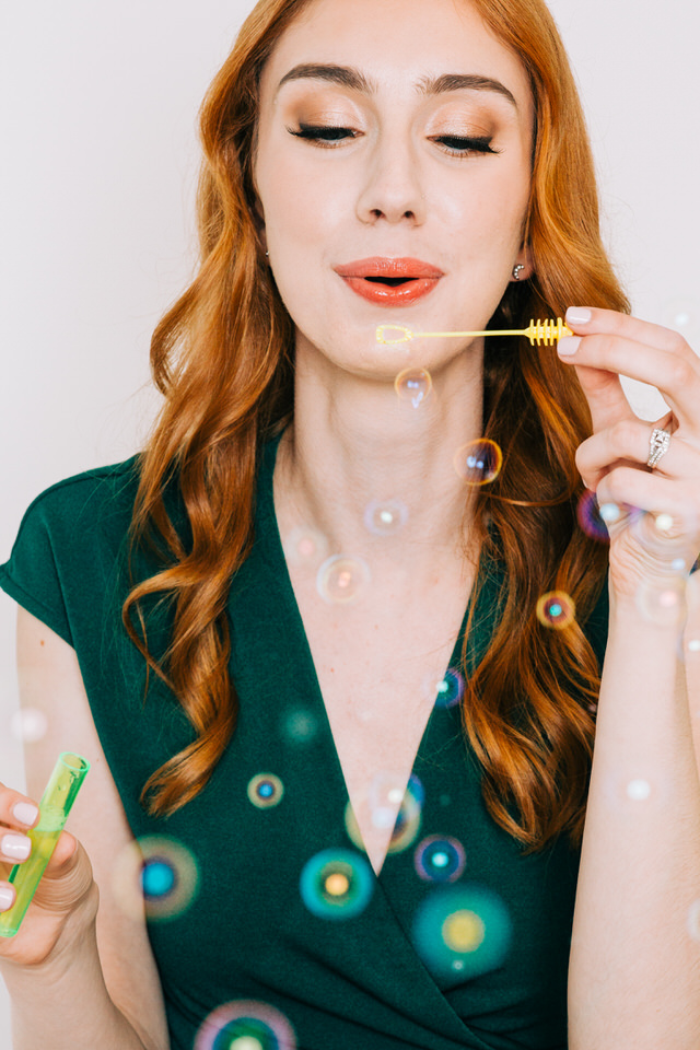 Woman with red hair blowing bubbles