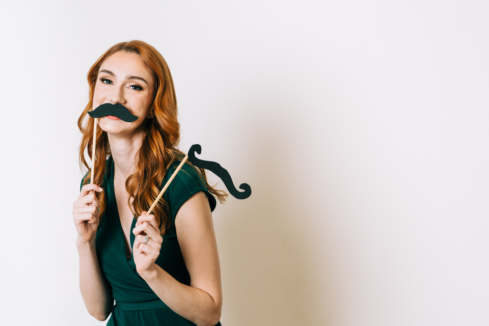 Woman with red hair holding onto and playing with mustache costume pieces