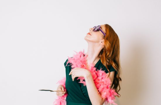 red headed woman wearing sunglasses, a feather boa