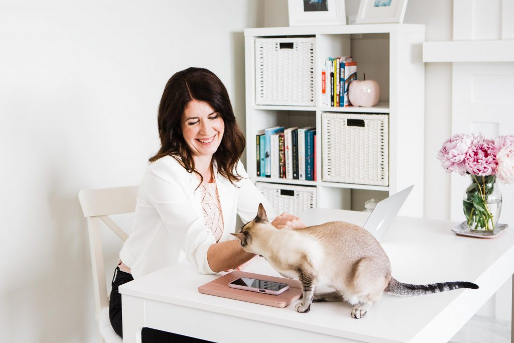 Woman sitting at her home office desk and petting her cat up on the desk