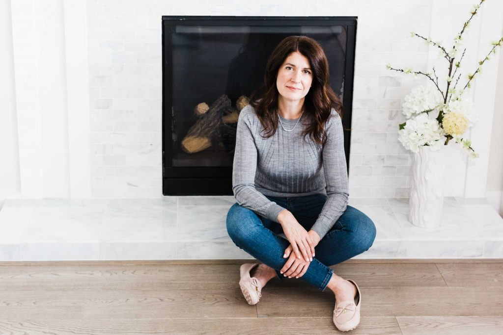 Woman sitting in front of a fire place wearing a gray sweater and jeans